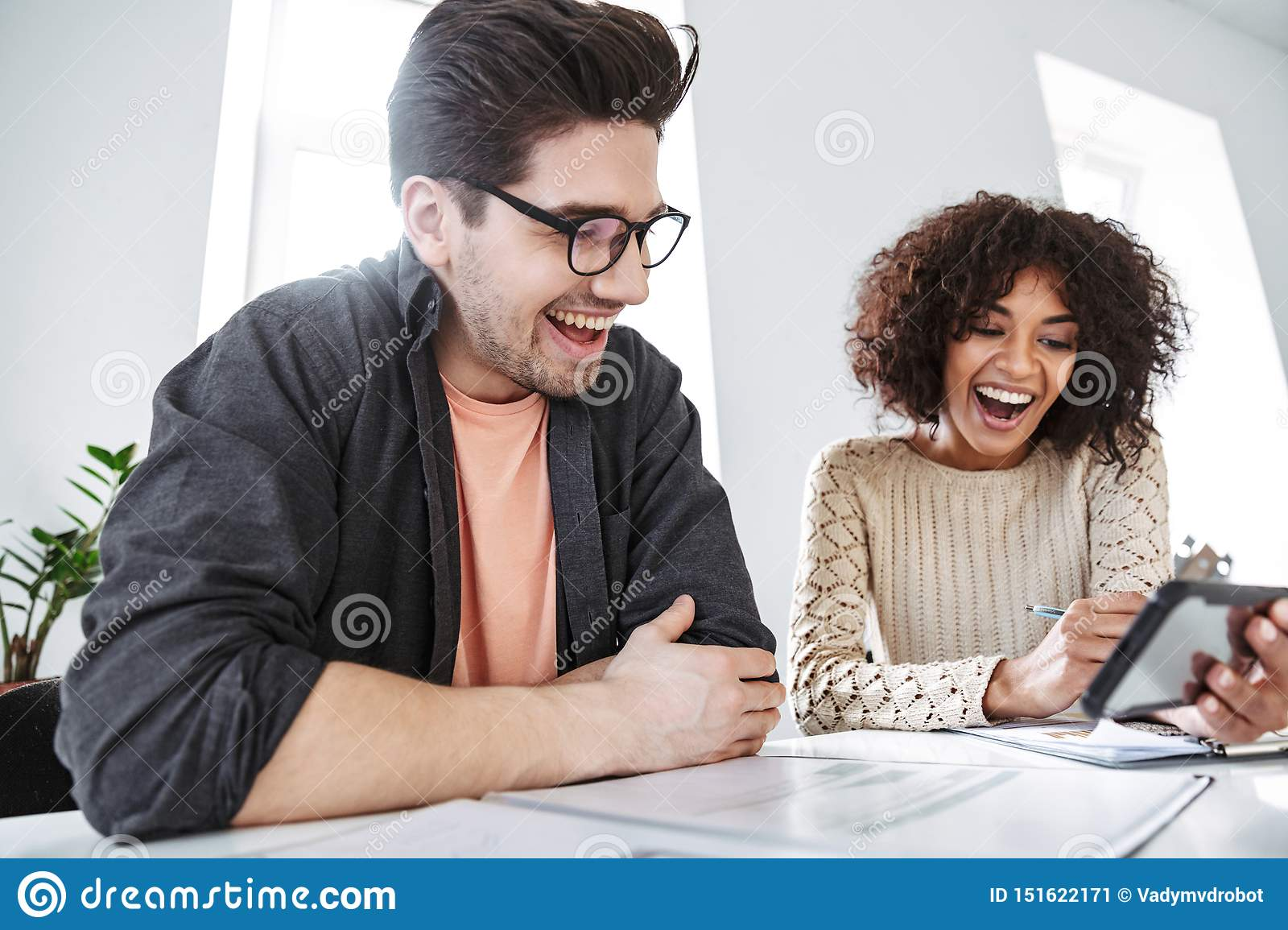 Side view of laughing young colleagues having fun together