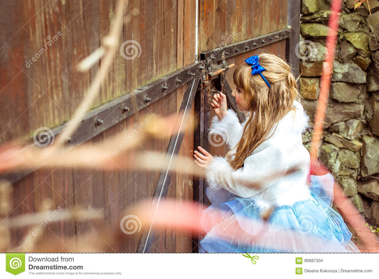 Side view of an little beautiful girl in the scenery of Alice in Wonderland looking into the keyhole of the gate
