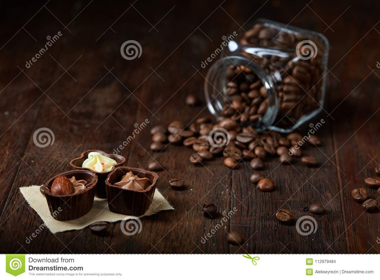 Side view of overturned glass jar with coffee beans and chocolate candies on wooden background, selective focus