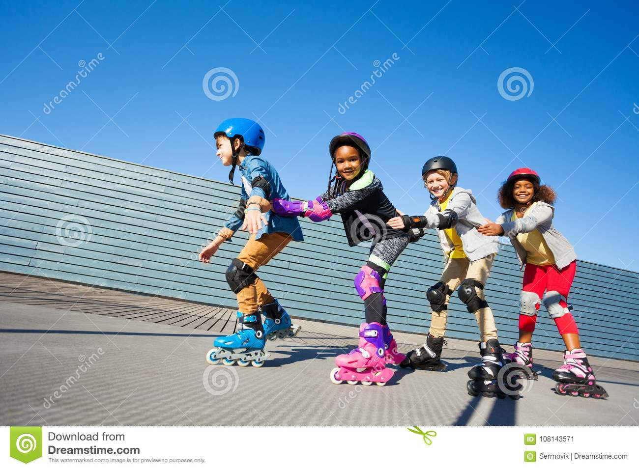 Cute kids rollerblading one after another outdoors