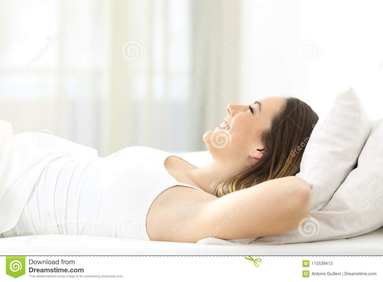 Happy woman resting lying on a bed looking up
