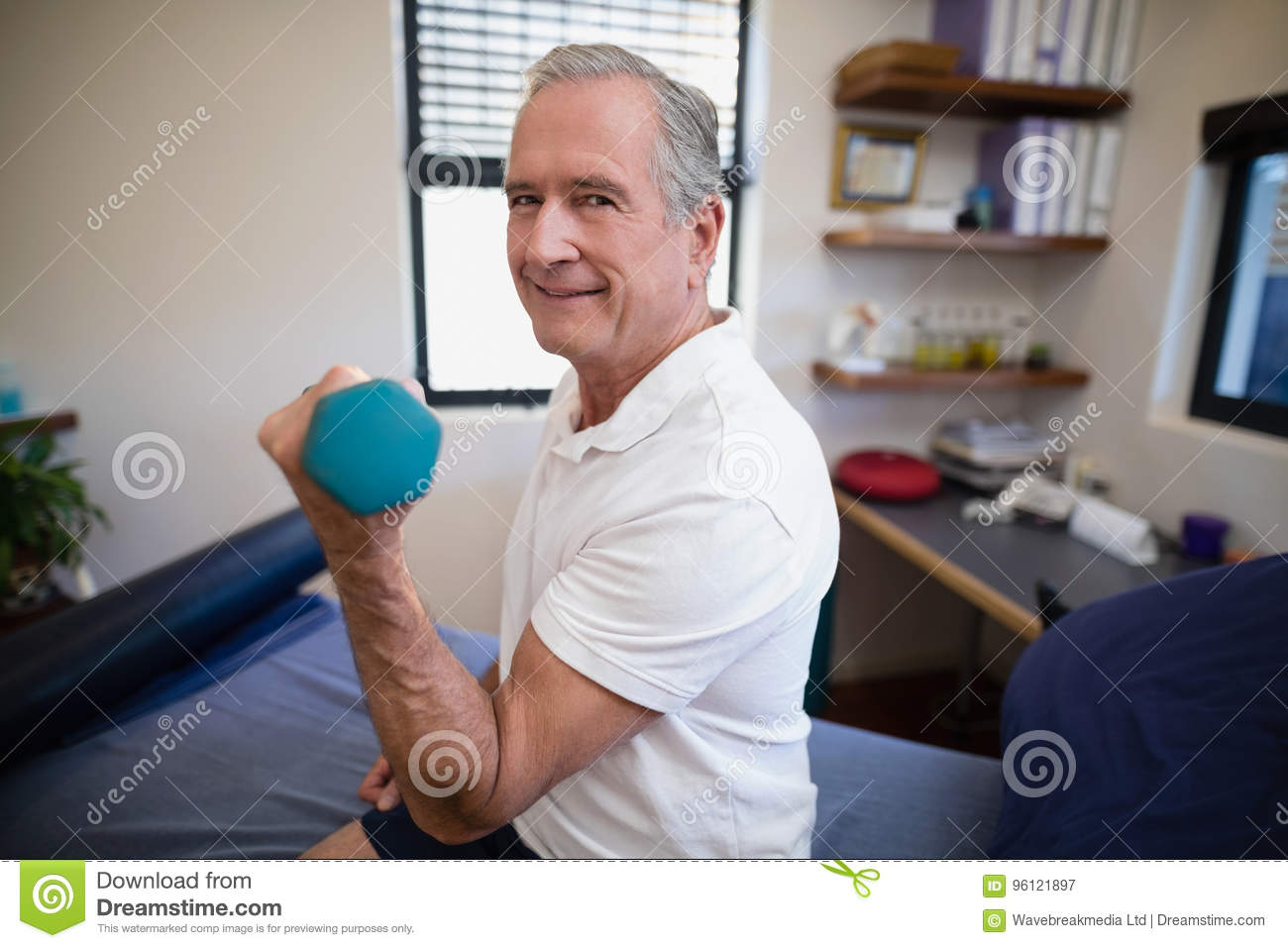 Side view portrait of smiling senior male patient lifting dumbbell