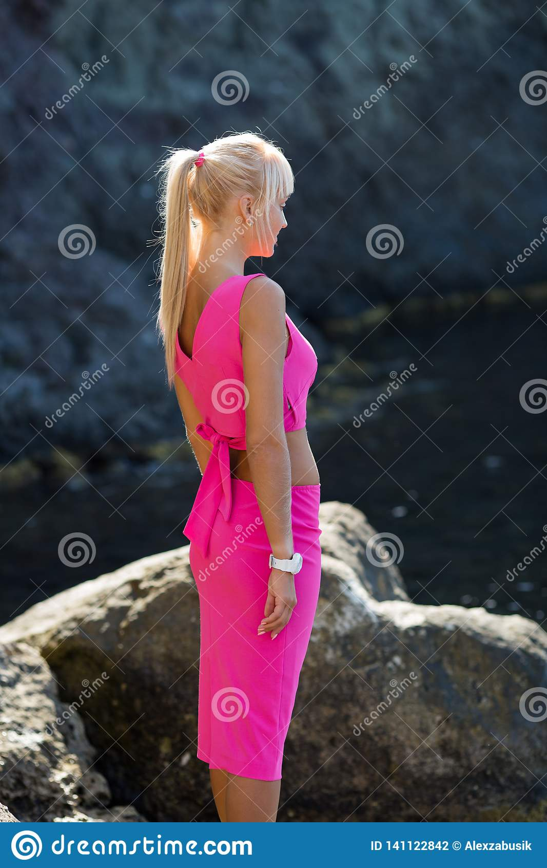 Side view portrait of woman in pink top and skirt against natural rocky cliff