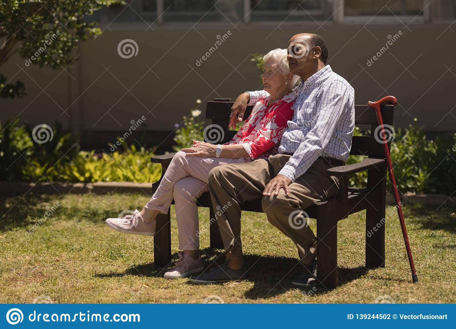 Side view of senior couple relaxing on bench in garden