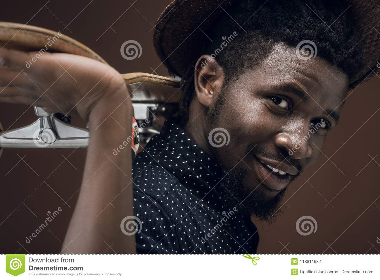 side view of smiling african american man with skate