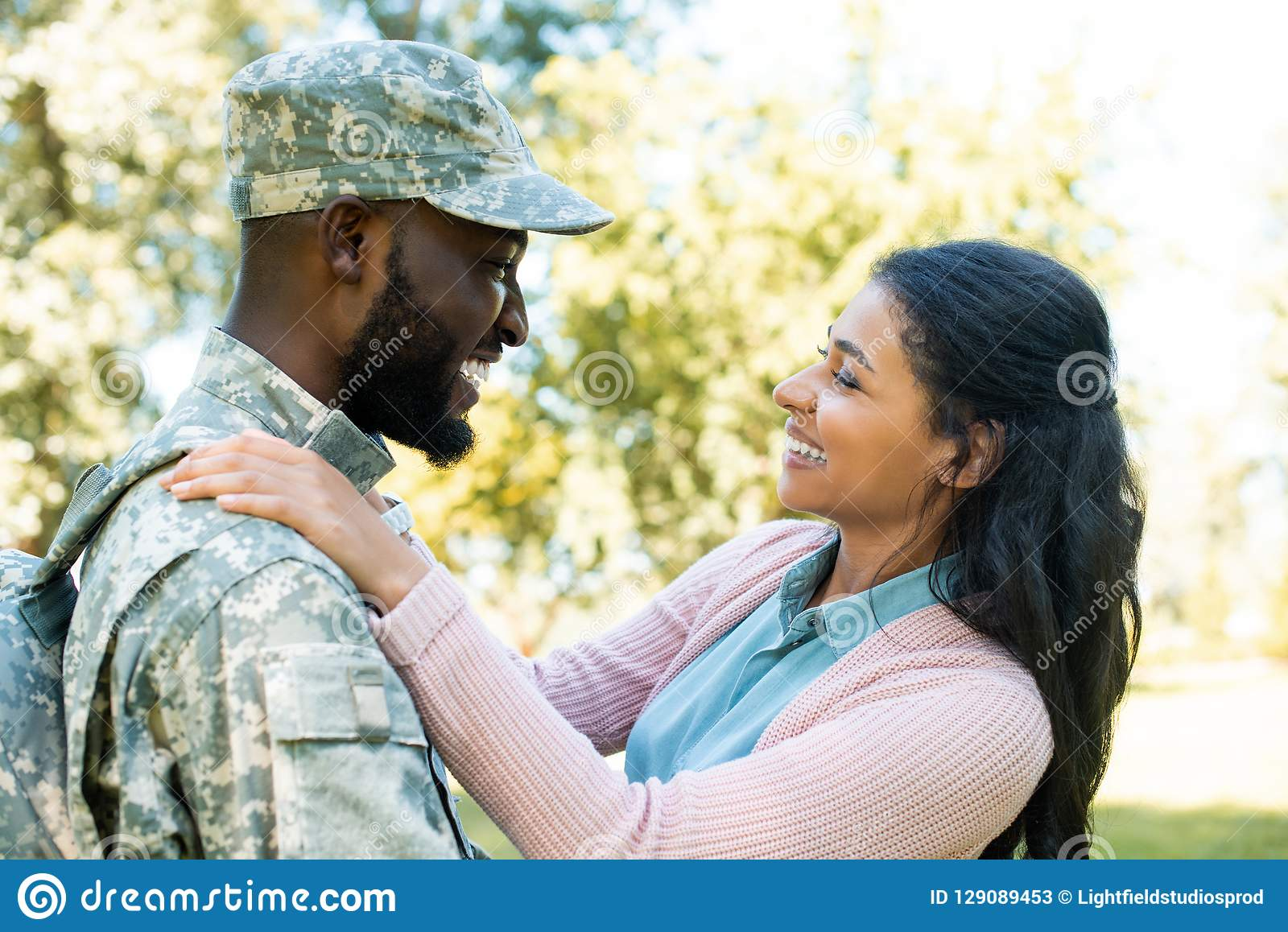 side view of smiling african american soldier in military uniform hugging girlfriend