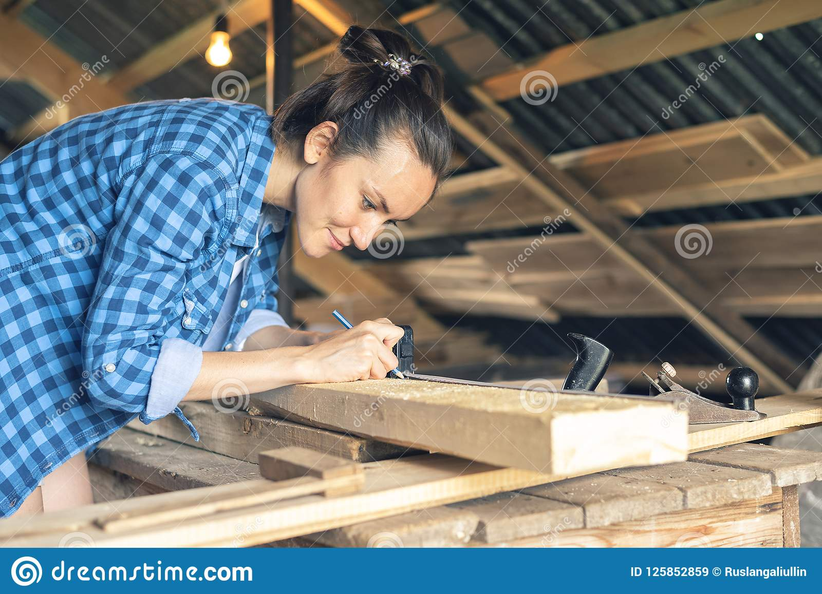 Side view of a woman carpenter draws on a wooden Board cut line