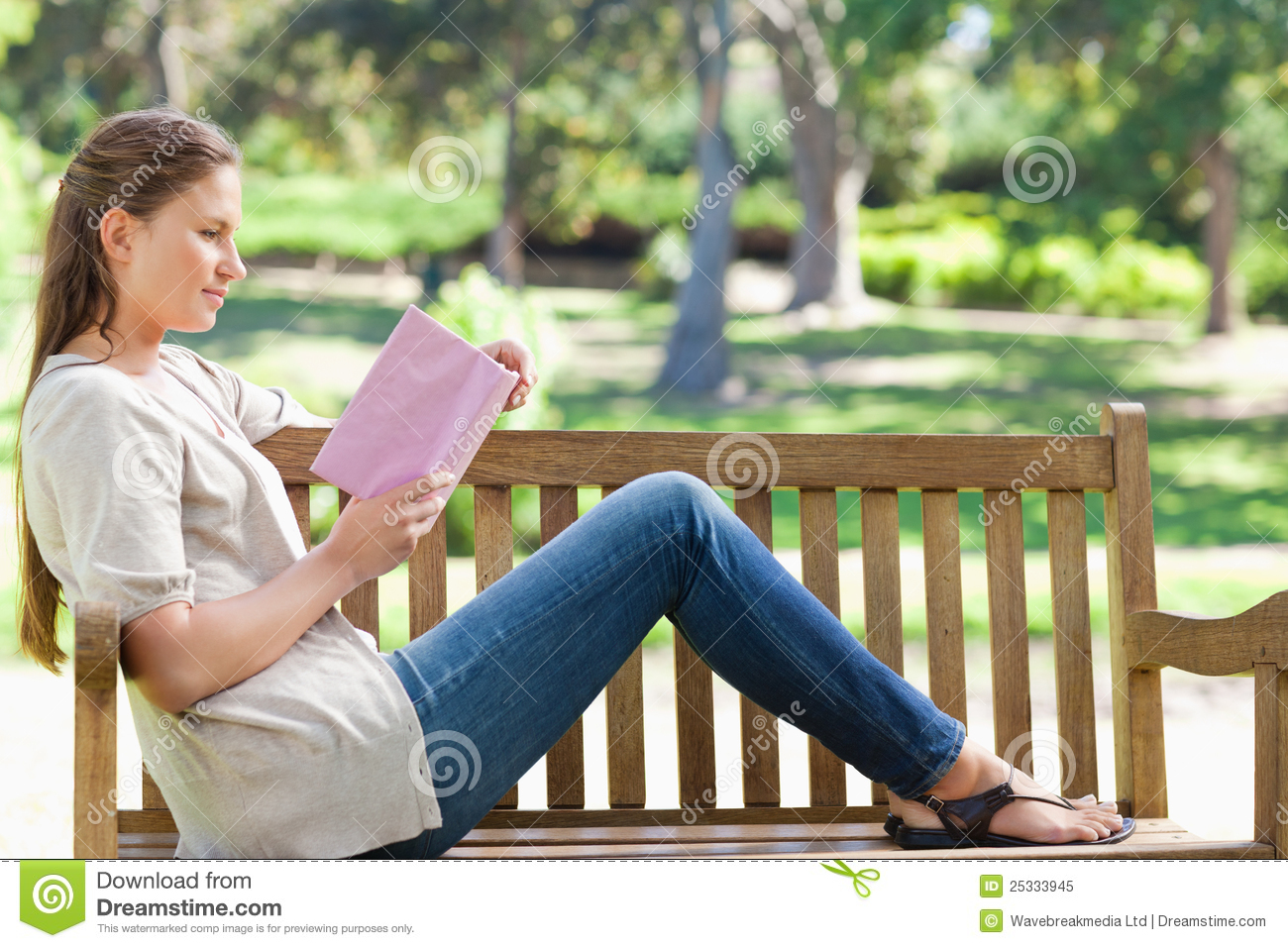 Side View Of A Woman Reading A Novel On A Park Bench Stock