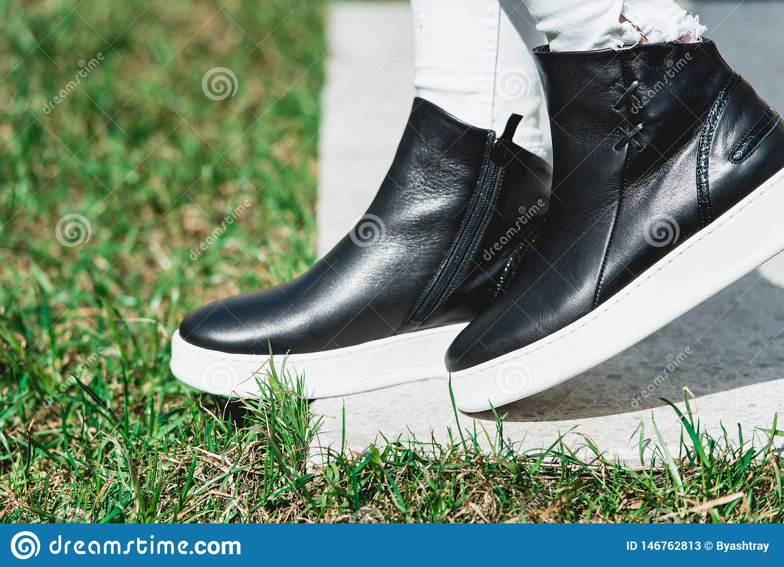 Side View Of Woman`s Black Leather Ankle Boots. Outdoor Shot Over White Stone in park