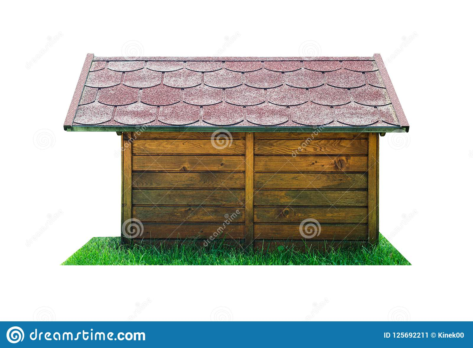 Side view of a wooden dog hut with a red roof, standing on the green grass. Isolated on a white background with a clipping path.