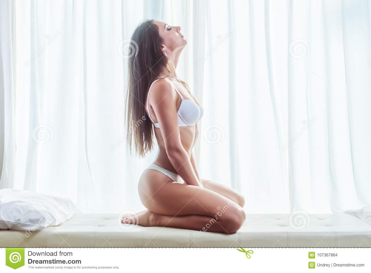 Side view of young brunette woman wearing lingerie sitting on white bed with window and curtains in background
