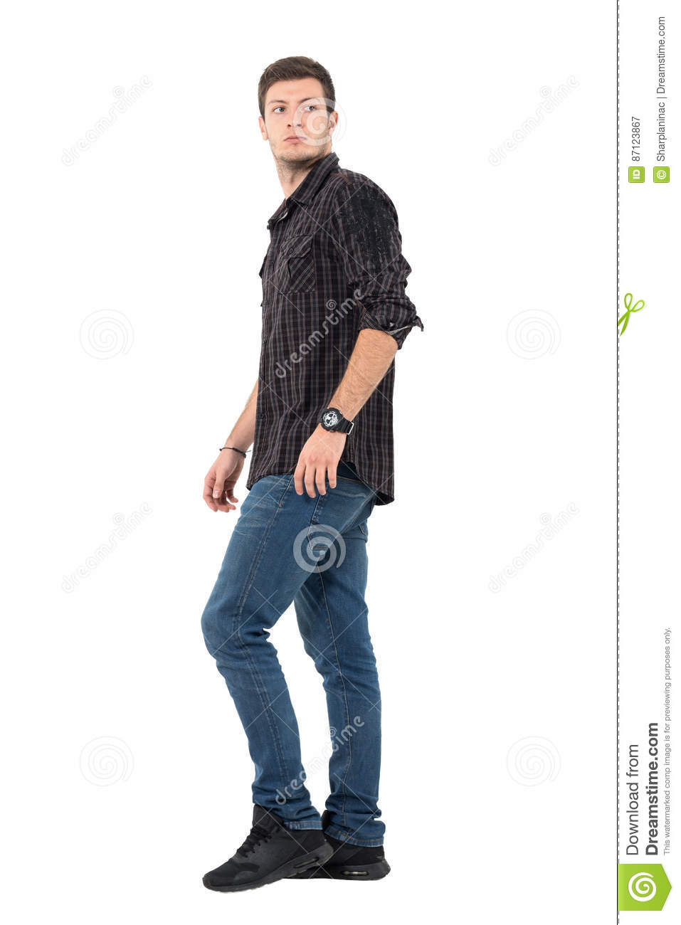 2b6693ca24 Side view of young casual man walking looking back over shoulder. Full body  length portrait isolated over white background.