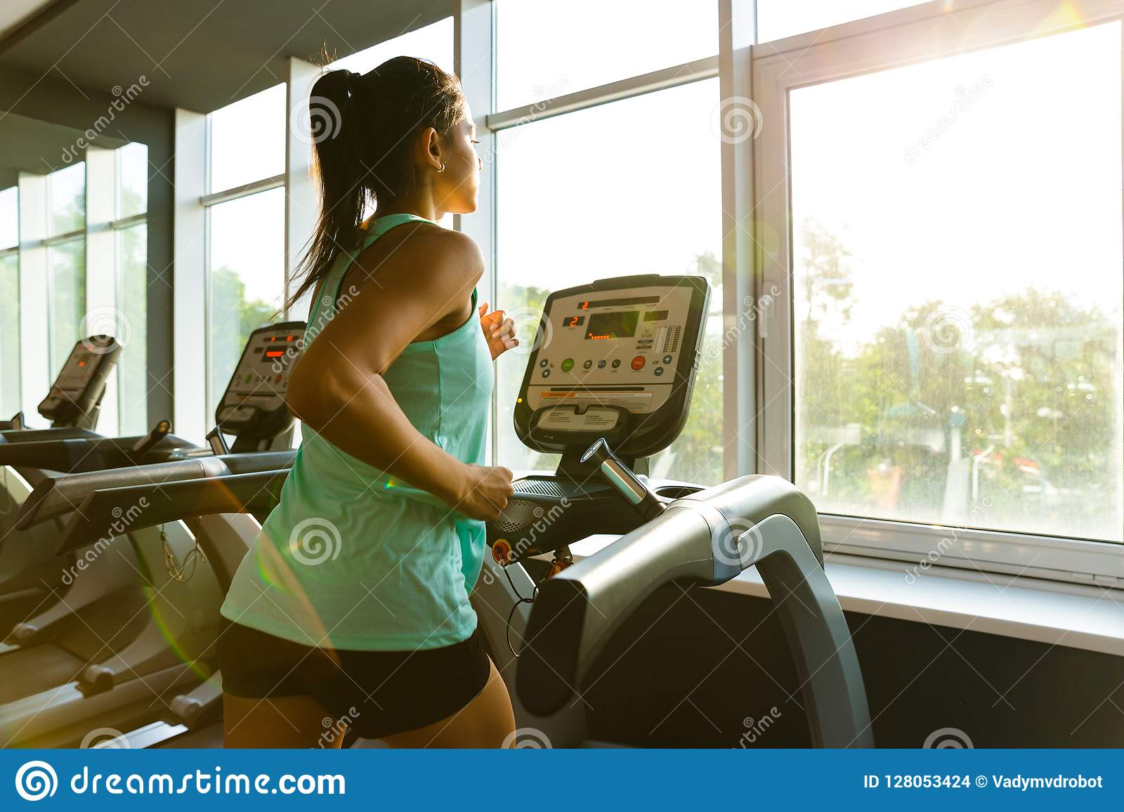 Side view of Young concentrated sports woman running on treadmill