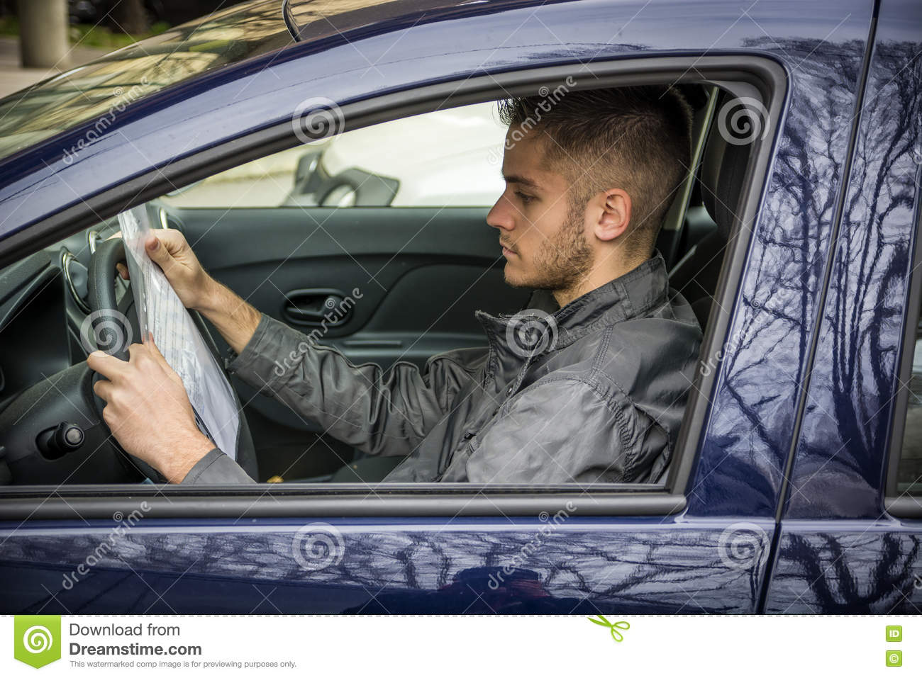 Side view of young driver reading document in car