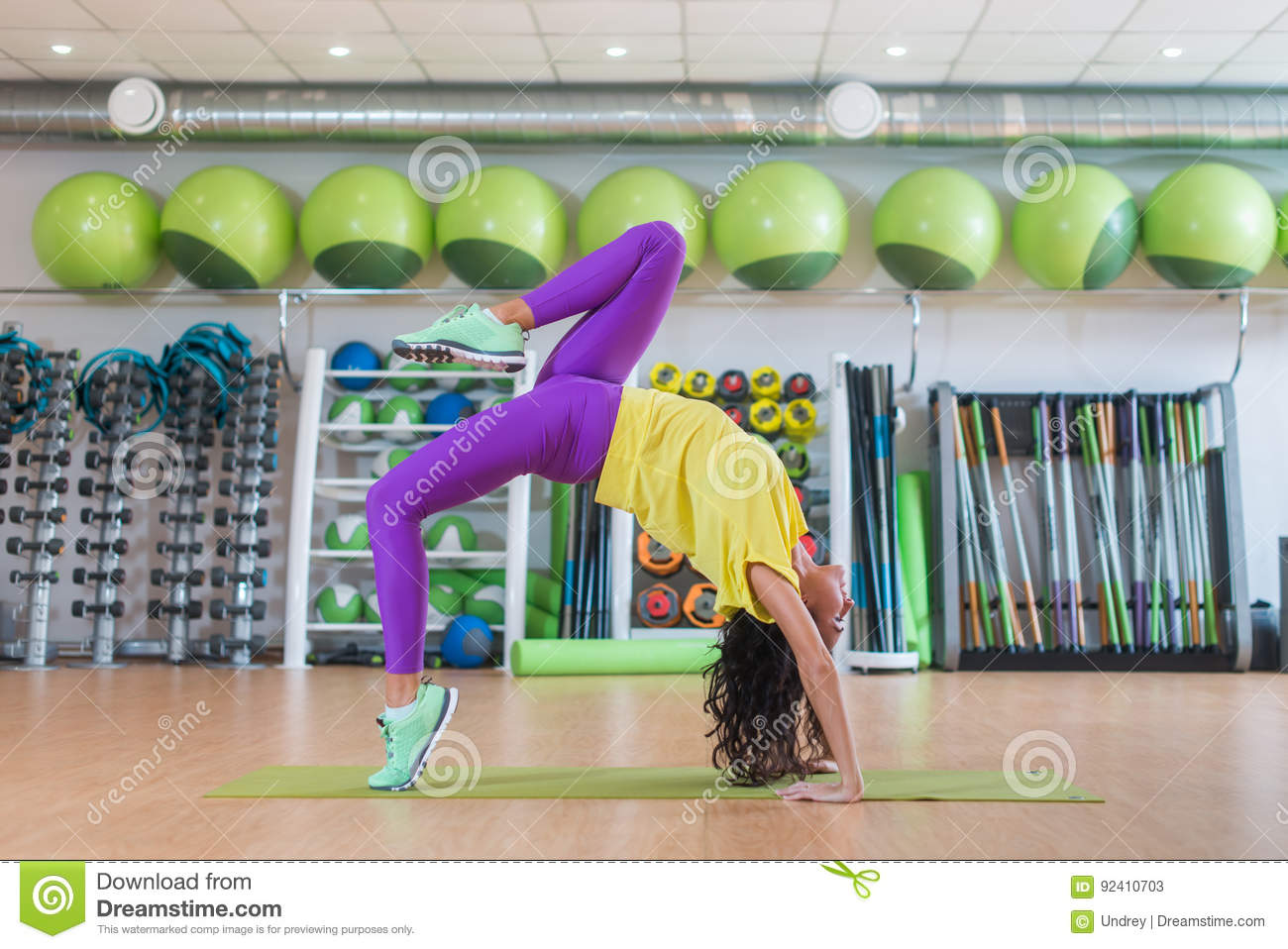 Side view of young female sportswoman doing yoga exercise standing in wheel pose in gym