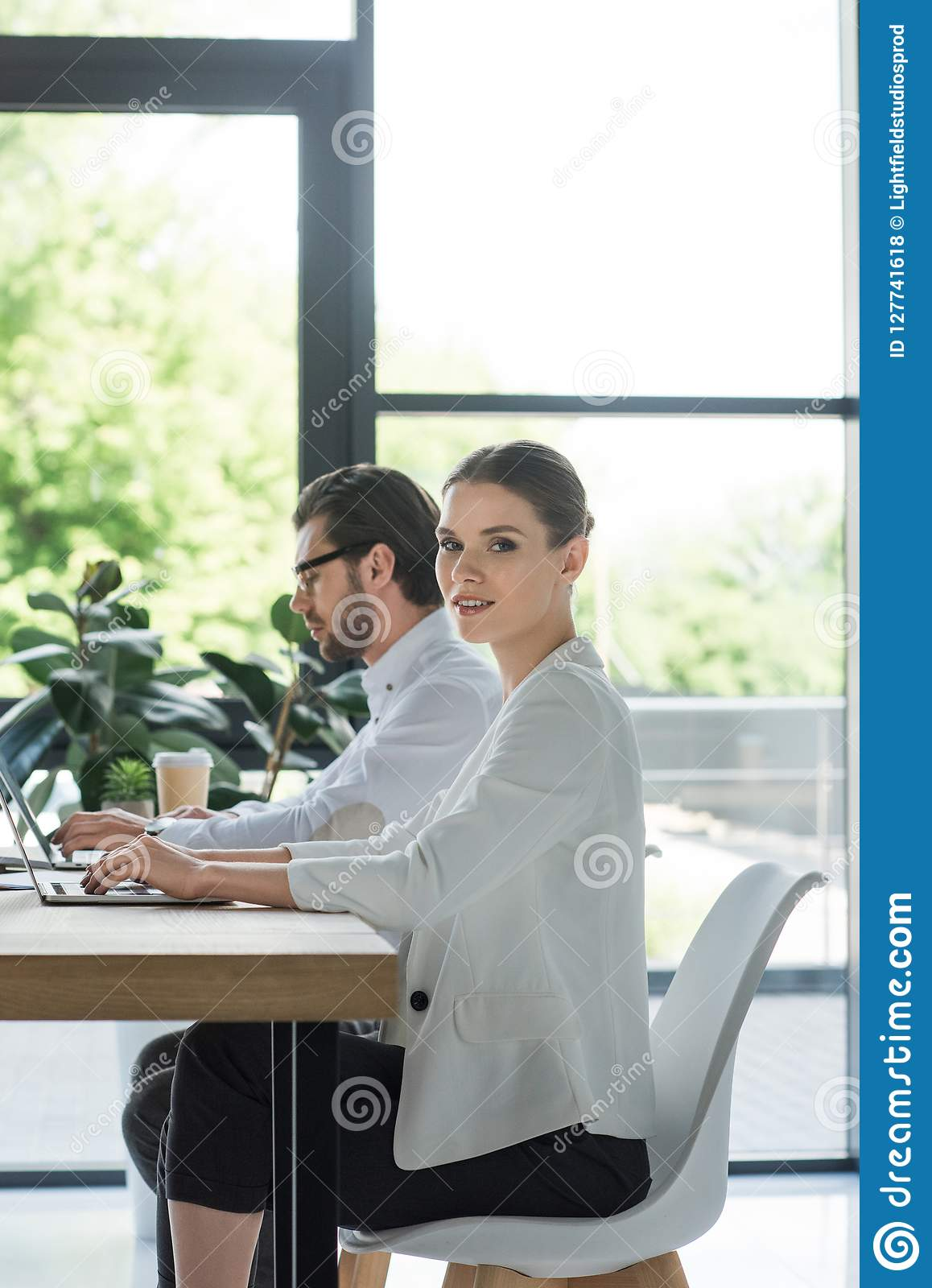side view of young successful managers working with laptops together