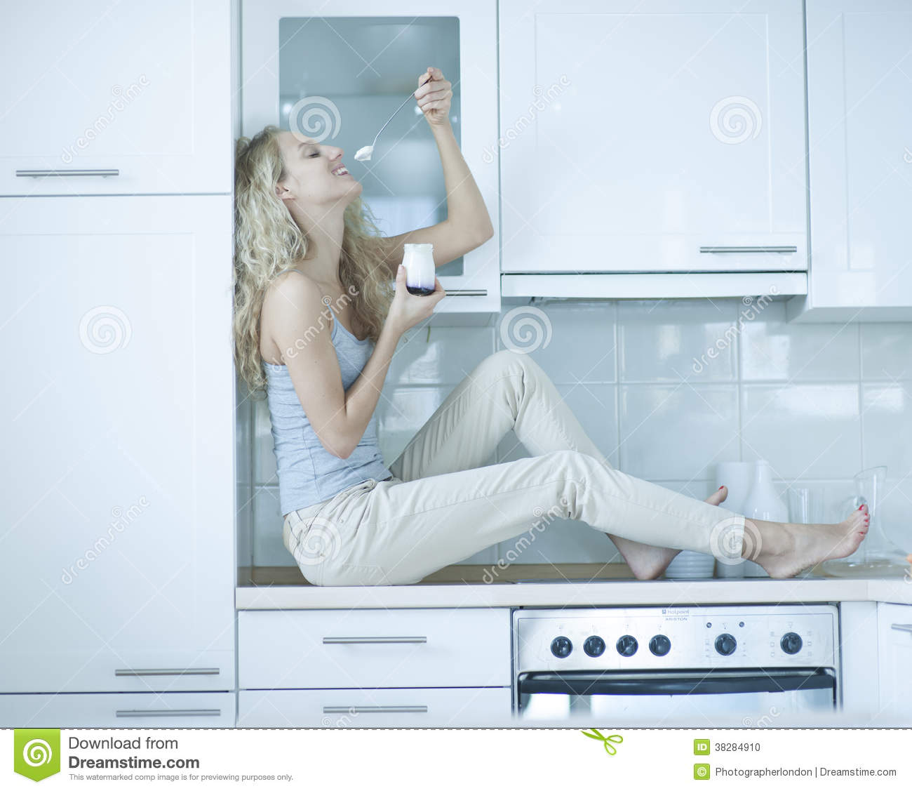 Side View Of Young Woman Eating Yogurt While Sitting On Kitchen ...