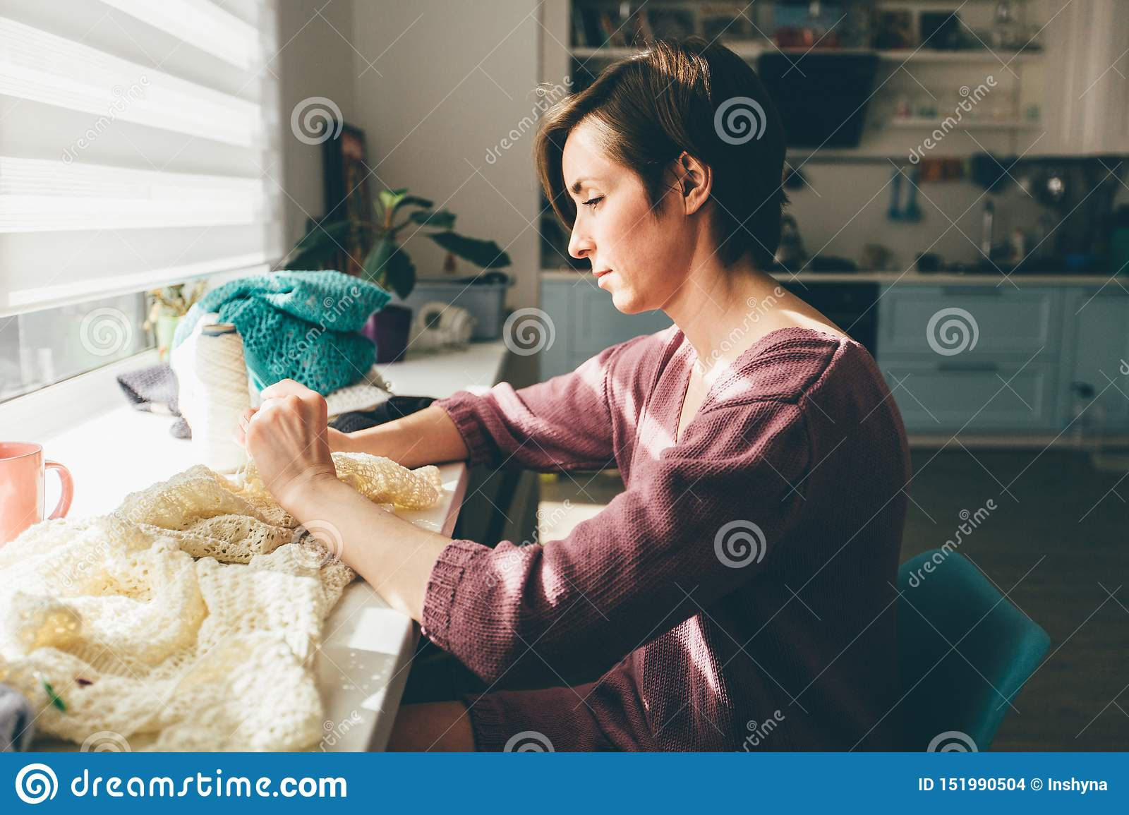 Side of woman knitting tender lace for tablecloth with crochet. Female freelancer creative working at cozy home workplace.