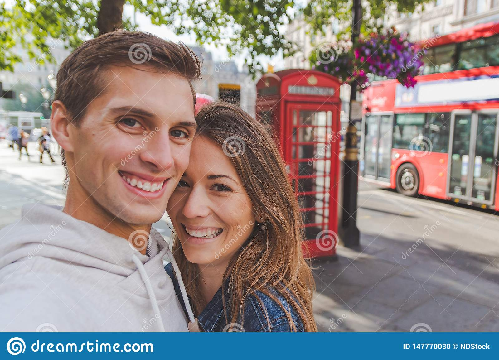 Happy young couple taking a selfie in front of a phone box and a red bus in London