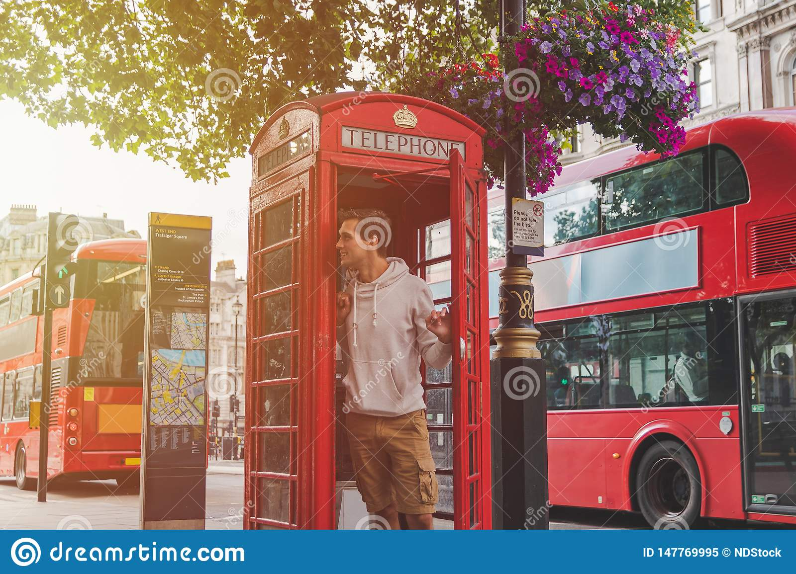 Young male in London looking out from a phone booth with red busses in the back