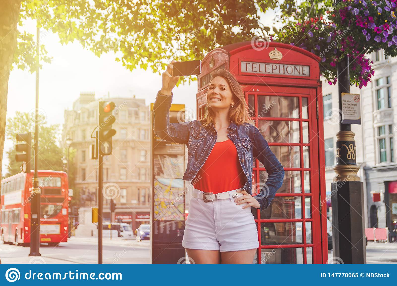 Happy young girl taking a selfie in front of a phone box and a red bus in London