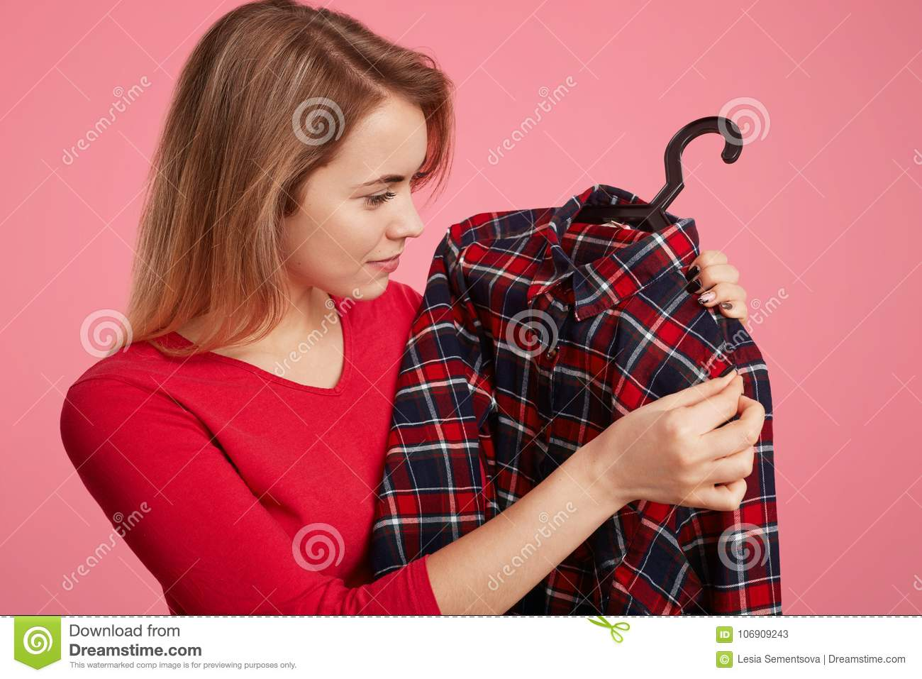 Sideways portrait of pleasant looking young female chooses new outfit, looks on checkered chemise on hangers, rejoice new purchase