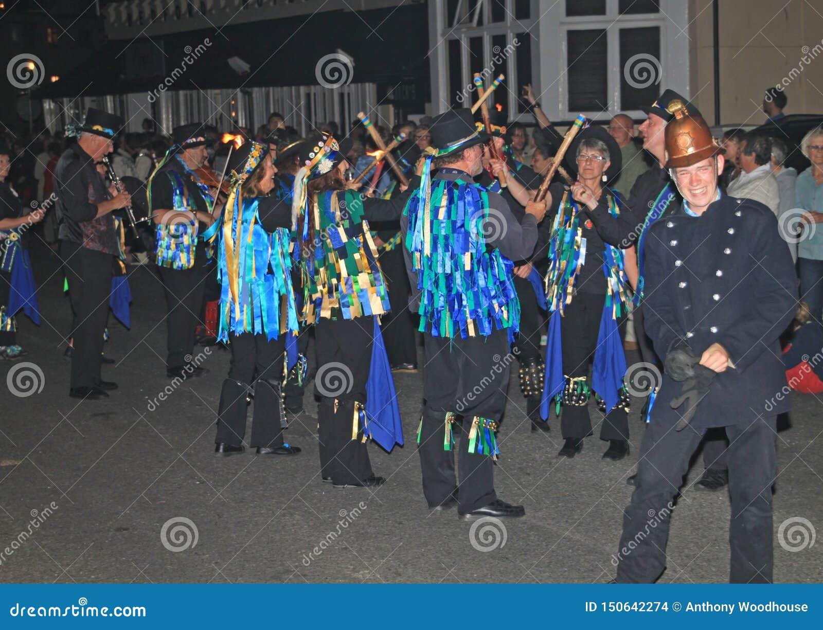 SIDMOUTH, ДЕВОН, АНГЛИЯ - 10-ОЕ АВГУСТА 2012: Группа в составе танцоры Моррис одетые в украшенных верхних шляпах и неровных голуб
