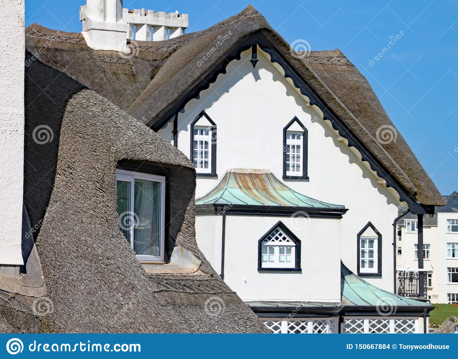 SIDMOUTH, ДЕВОН - 1-ОЕ АПРЕЛЯ 2012: Красивая старая покрыванная соломой резиденция стоит на побережье Sidmouth на солнечный день