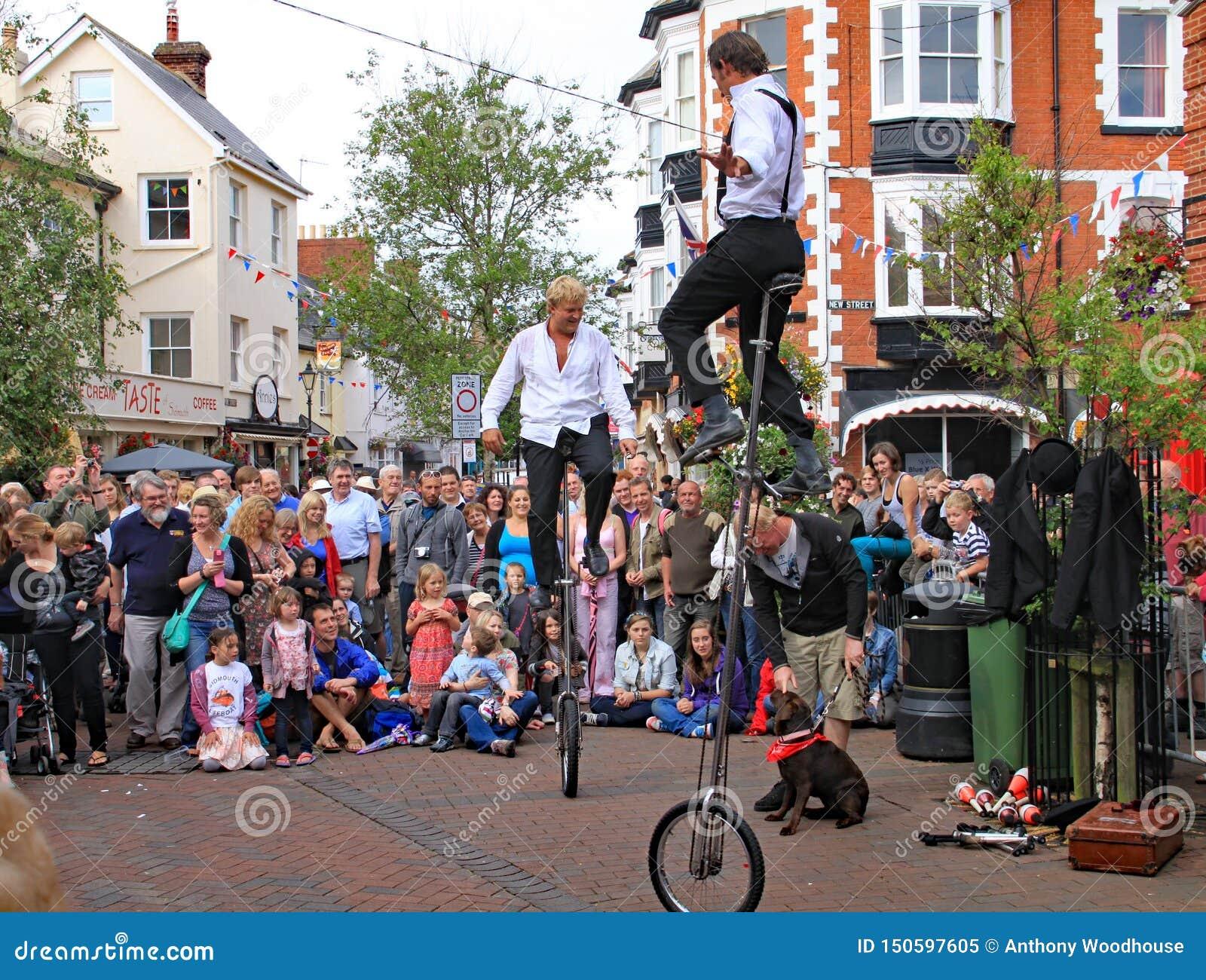 SIDMOUTH, DEVON ANGLIA, SIERPIEŃ, - 5TH 2012: Dwa ulicznego artysty estradowego i jugglers wykonują w rynku doceniający