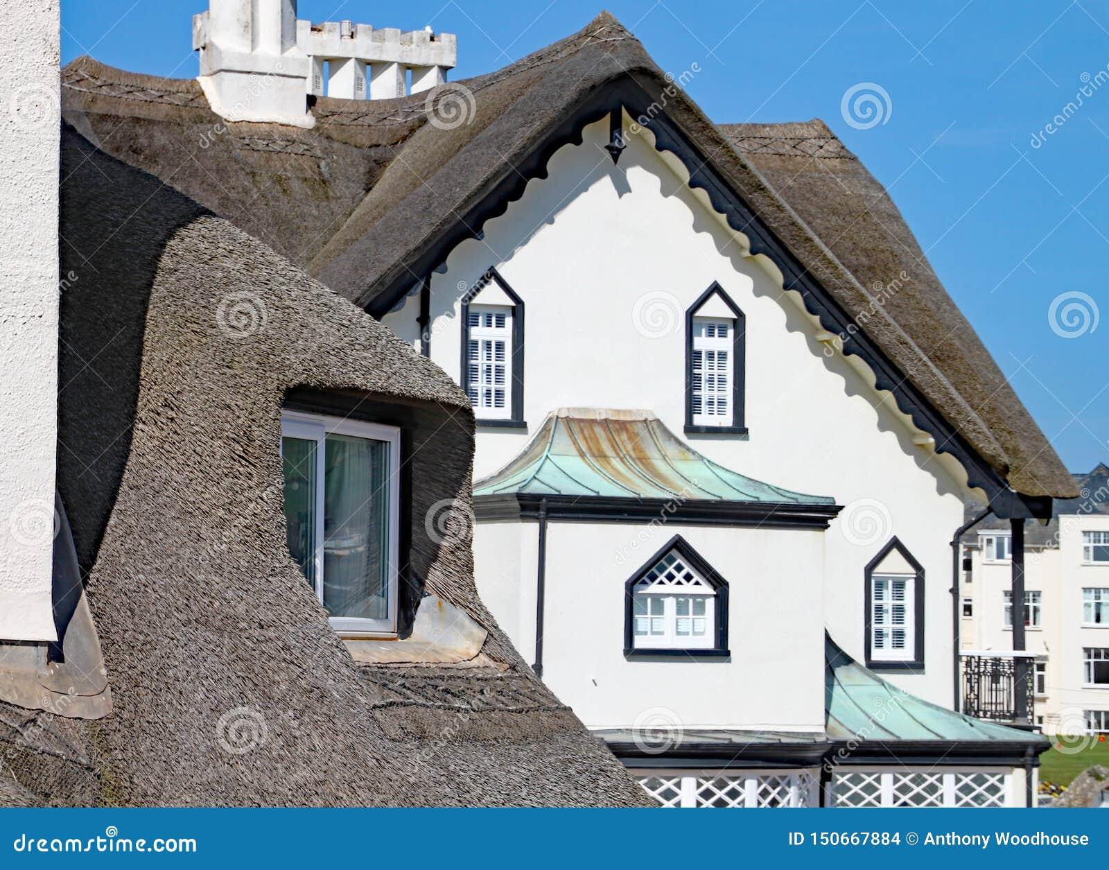 SIDMOUTH, DEVON - 1. APRIL 2012: Der schöne alte mit Stroh gedeckte Wohnsitz steht auf der Sidmouth-Küste an einem sonnigen Tag
