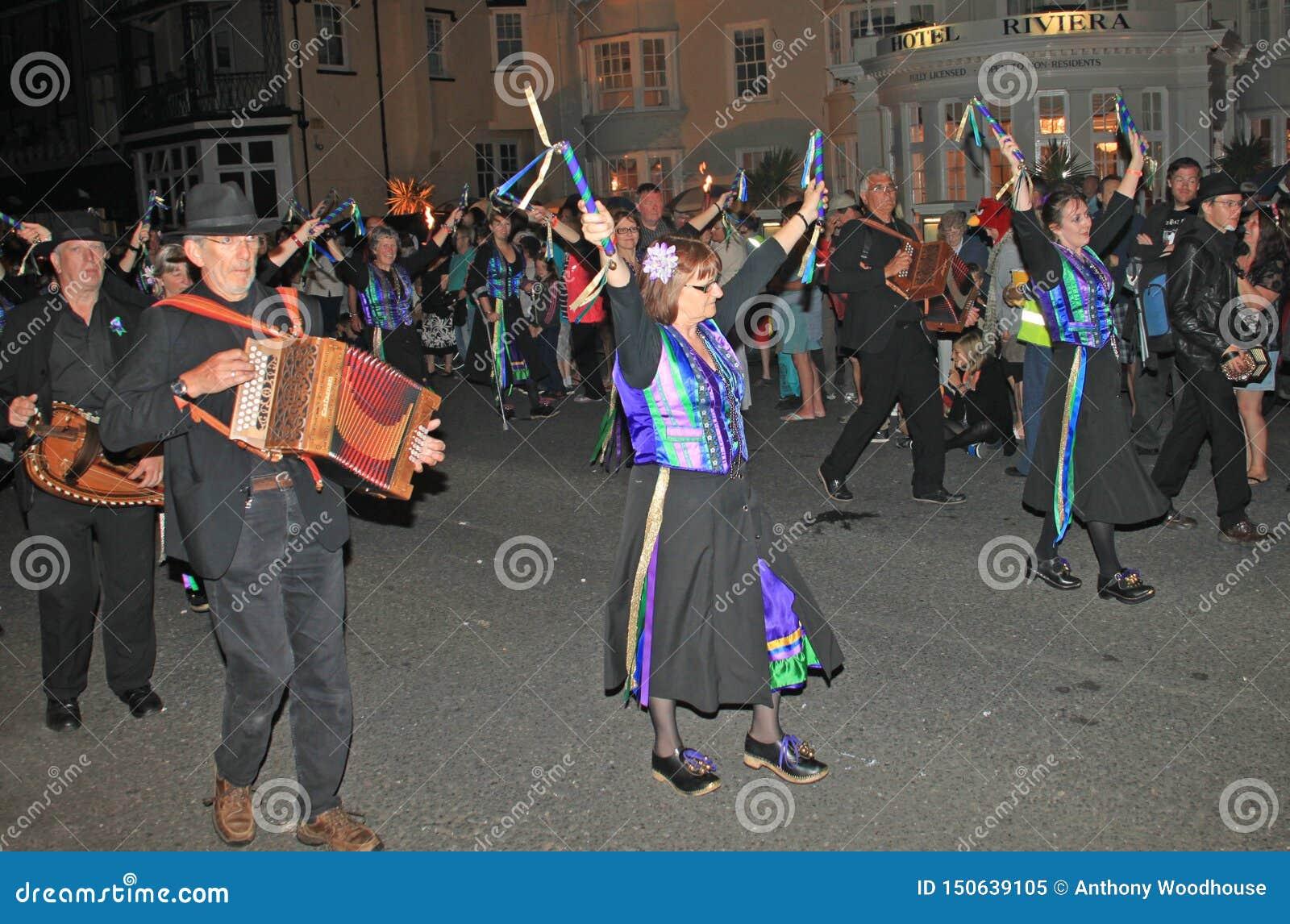SIDMOUTH, DEVON, ENGELAND - AUGUSTUS TIENDE 2012: Een groep musici en belemmeringsdansers kleedde zich in hun mauve en groen en h