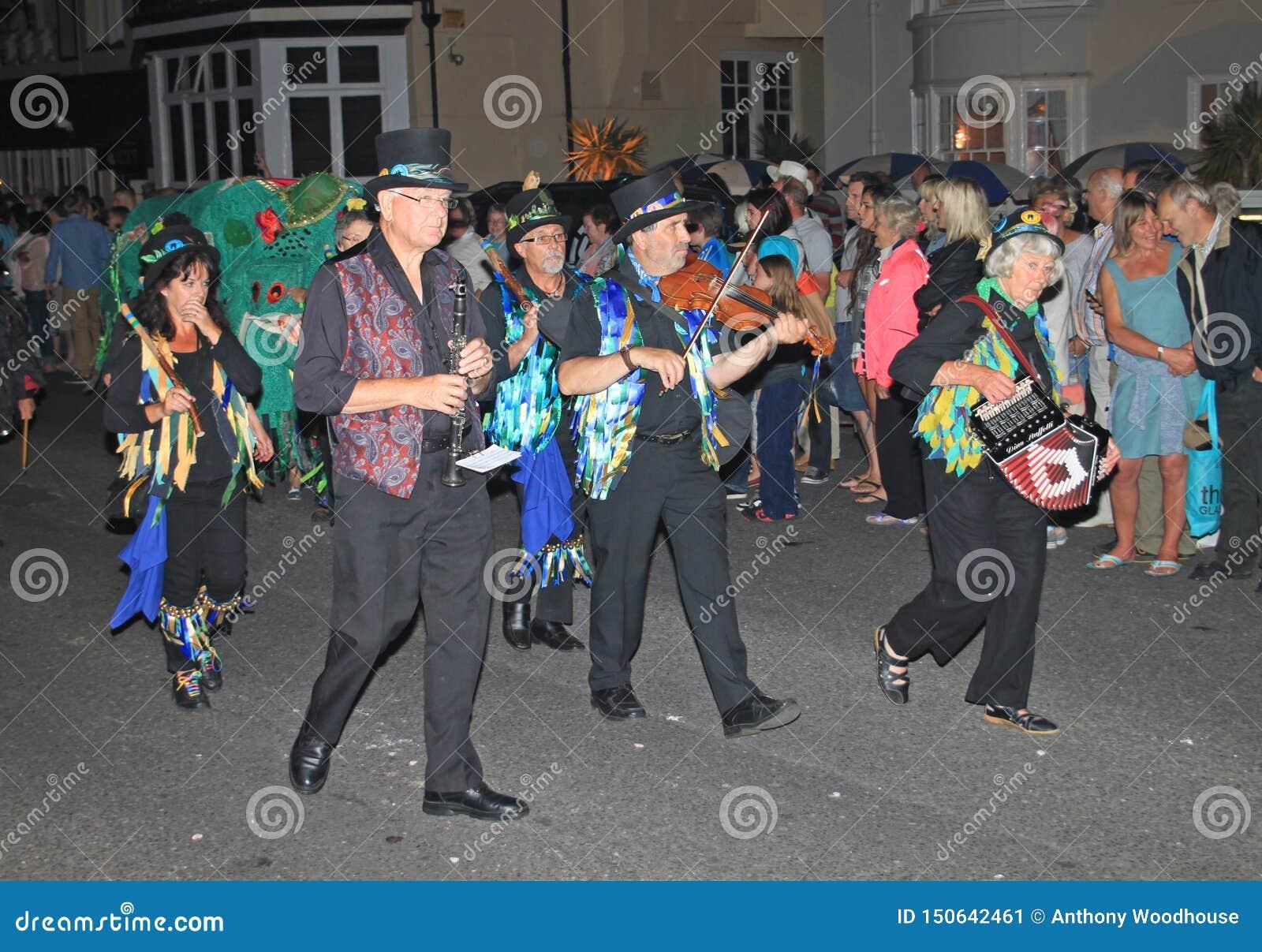 SIDMOUTH, DEVON, ENGELAND - AUGUSTUS TIENDE 2012: Een groep musici gekleed in verfraaide hoge zijden en de haveloze blauwe vesten