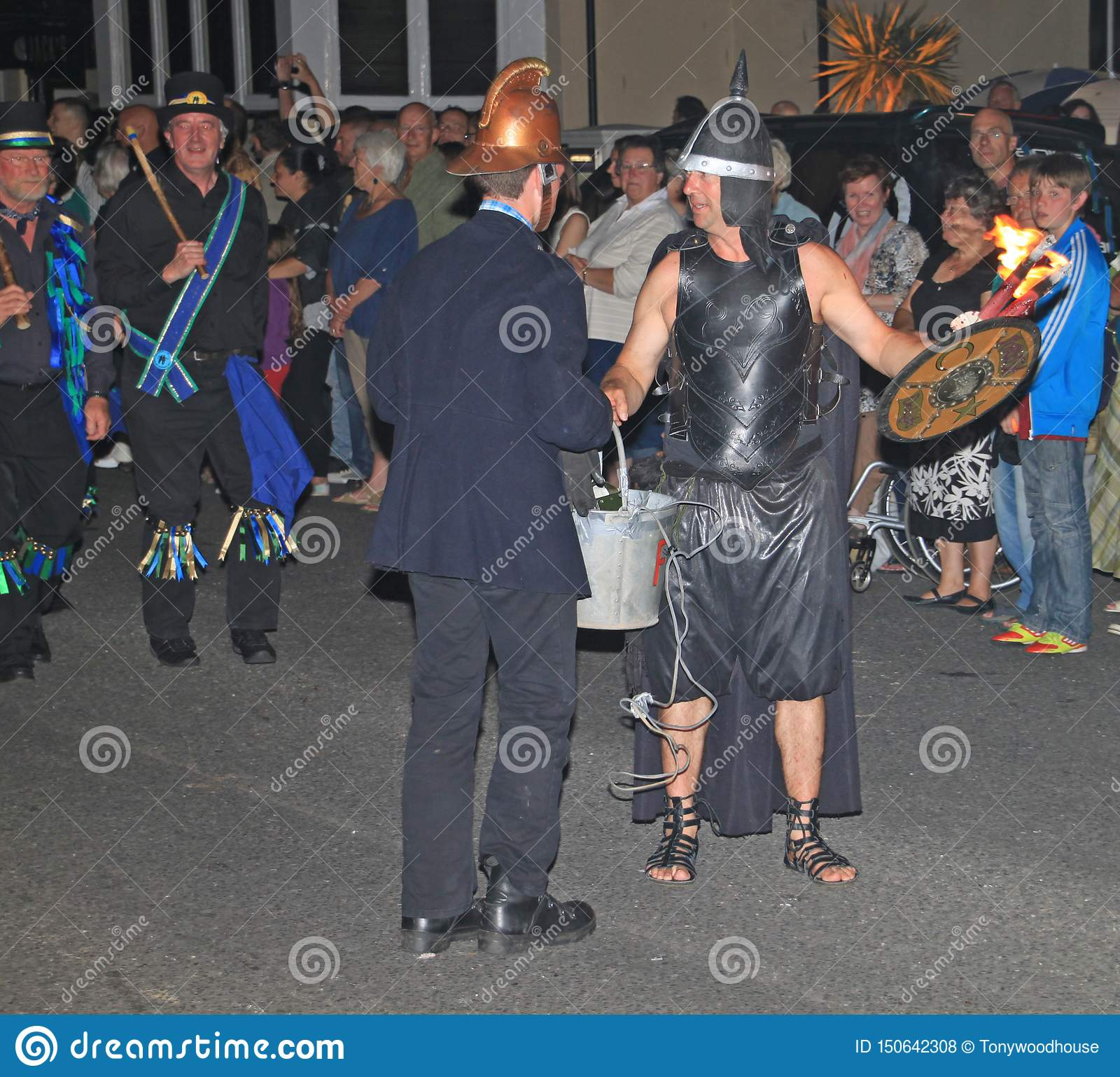 SIDMOUTH, DEVON, ENGLAND - AUGUST 10TH 2012: A man dressed as a fireman and another dressed as an ancient warrior take part in the