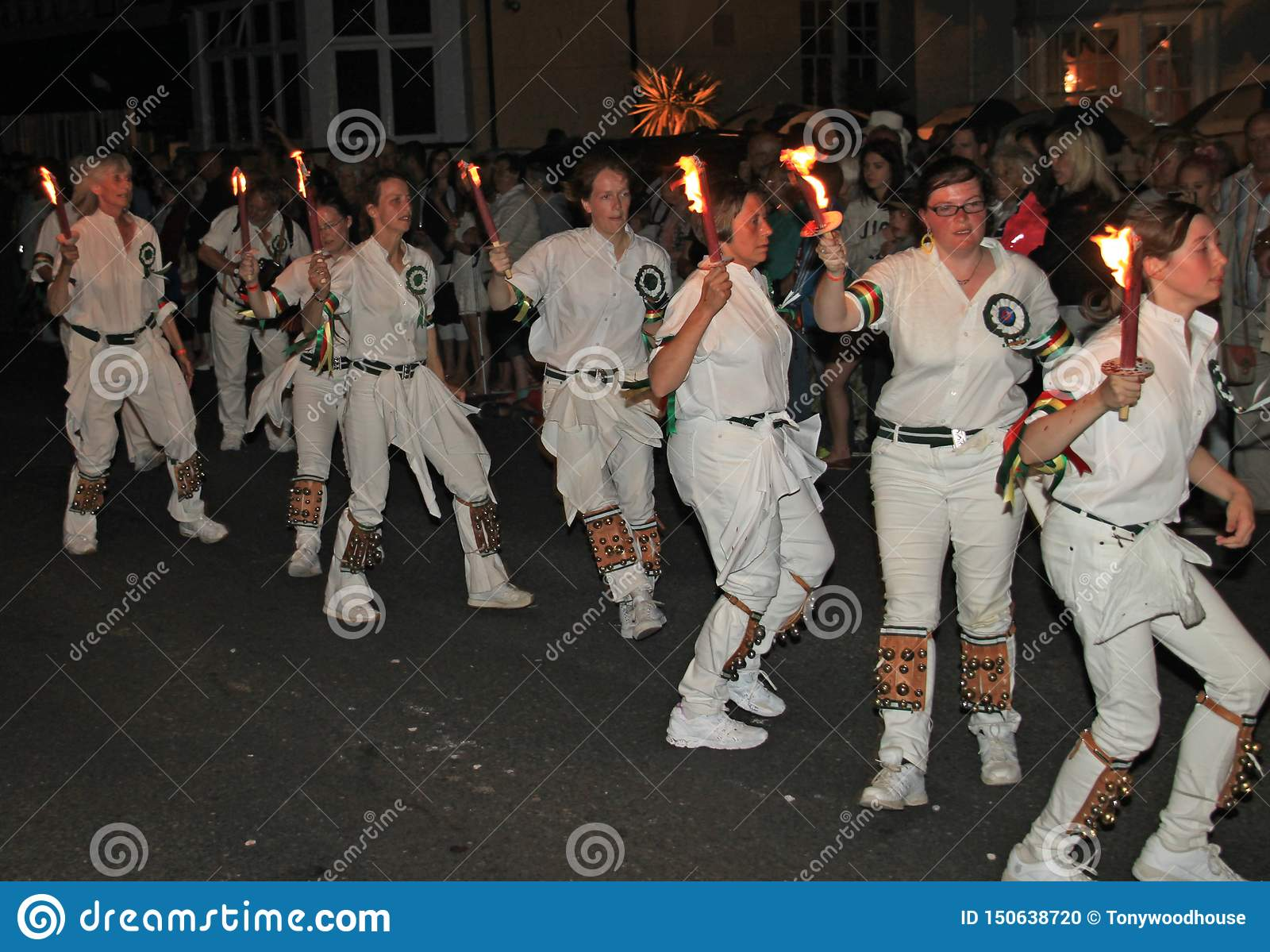 SIDMOUTH, DEVON, ENGLAND - AUGUST 10TH 2012: A troup of young lady Morris dancers hold their flaming torches as they takes part in