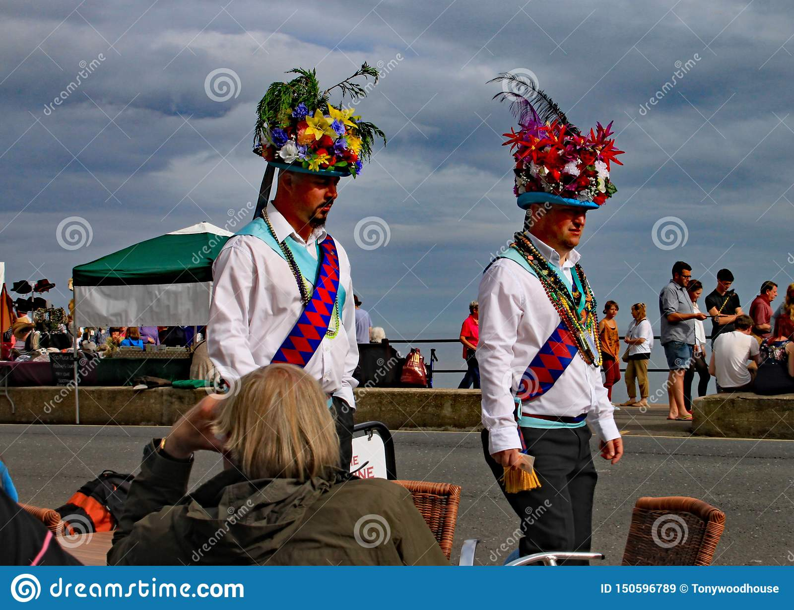 SIDMOUTH, DEVON, ENGLAND - AUGUST 8TH 2012: Two Morris dancers in extravagant head gear walk along the Esplanade during folk week