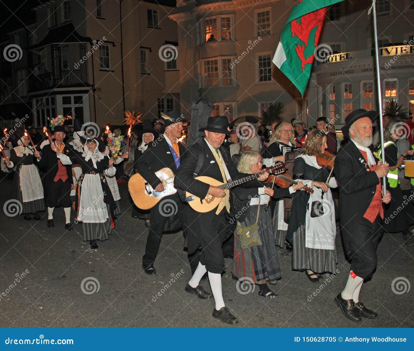 SIDMOUTH DEVON, ENGLAND - AUGUSTI 10TH 2012: En grupp av walesiska aktörer tar delen i nattetidbokslutprocessionen av folk