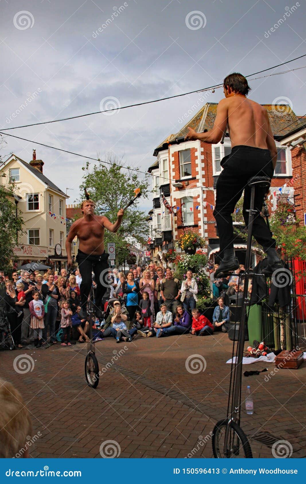 SIDMOUTH DEVON, ENGLAND - AUGUSTI 5TH 2012: Två gatajonglörer och underhållare utför med enhjulingar och brandklubbor i staden