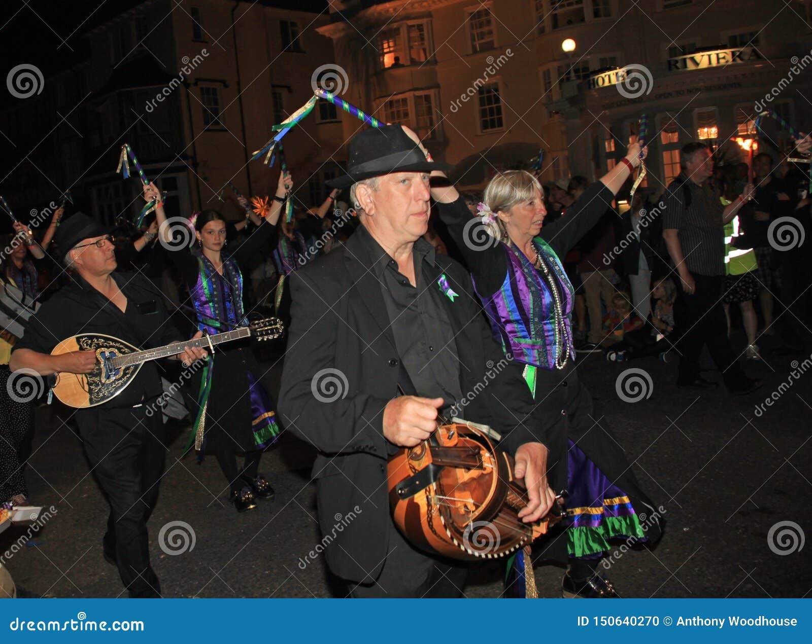 SIDMOUTH, DEVON, INGHILTERRA - 10 AGOSTO 2012: Un gruppo di musicisti ed i ballerini dell impedimento vestiti nel malva e nel ver