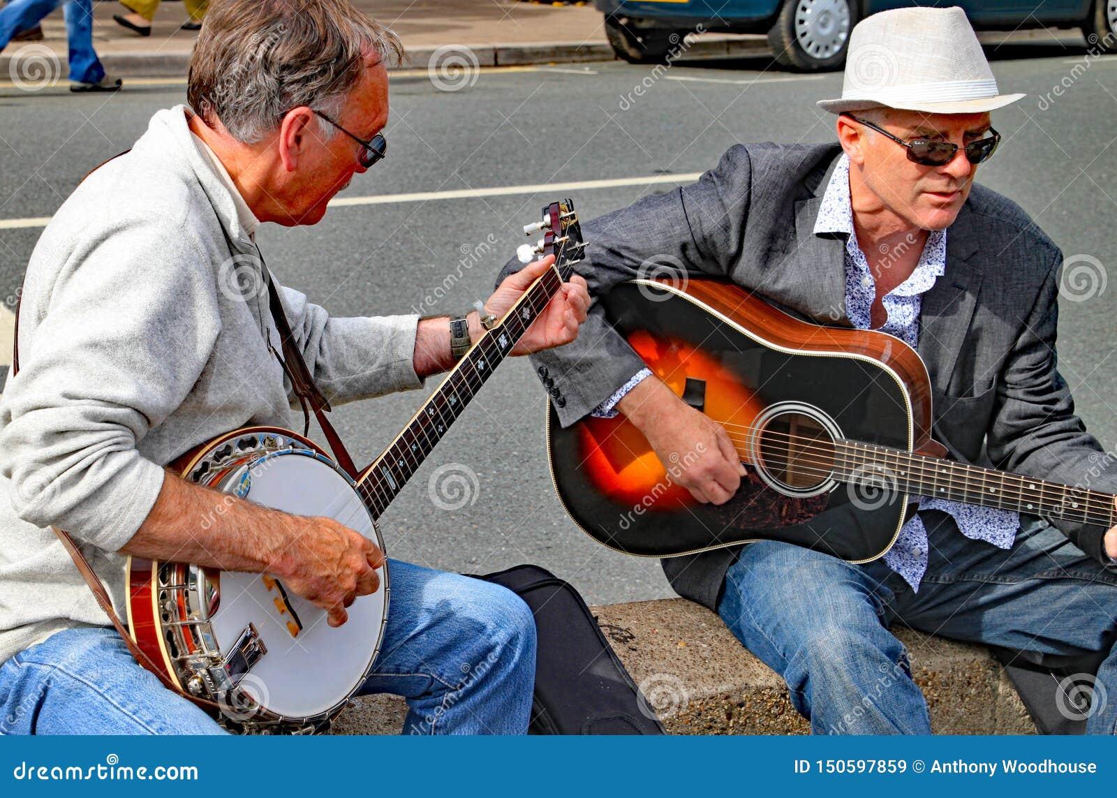 SIDMOUTH, DEVON, INGLATERRA - 8 DE AGOSTO DE 2012: Dos hombres tocan una guitarra y un banjo en un funcionamiento improvisado de