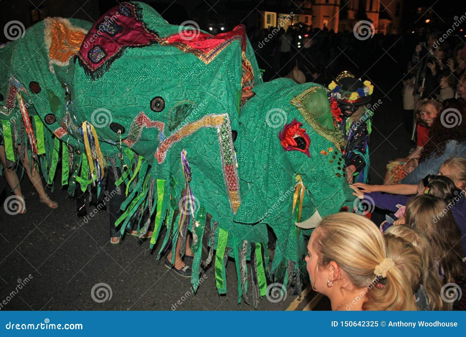 SIDMOUTH, DEVON, INGLATERRA - 10 DE AGOSTO DE 2012: Um dragão chinês verde obtém afagado por espectadores enquanto participa na n
