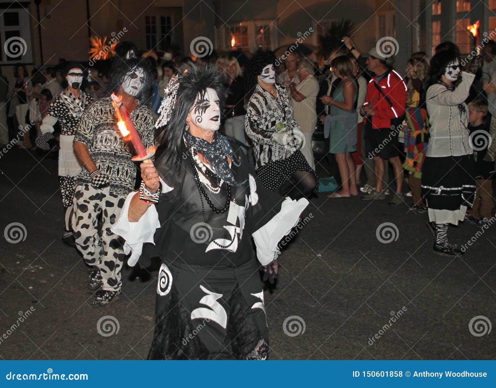 SIDMOUTH, DEVON, INGLATERRA - 10 DE AGOSTO DE 2012: Um troup da dança vestido em trajes preto e branco muito deléveis participa n