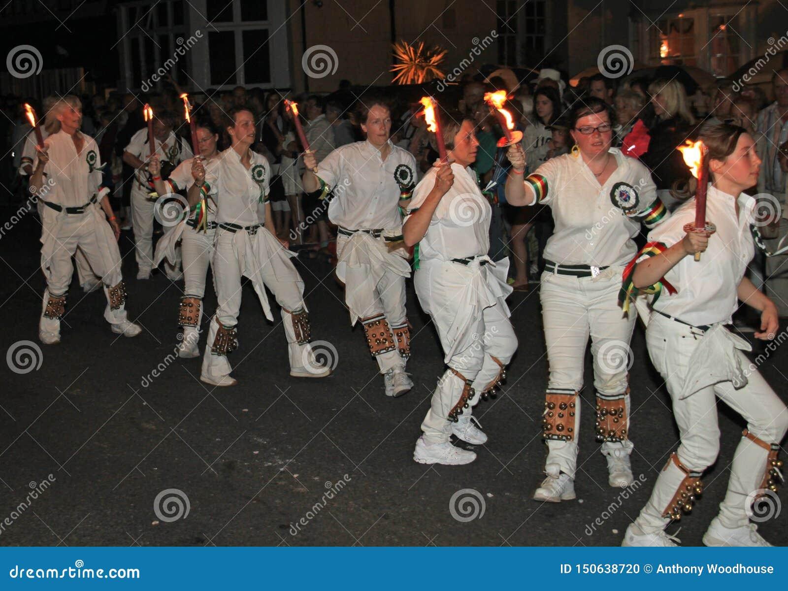 SIDMOUTH, DEVON, INGLATERRA - 10 DE AGOSTO DE 2012: Um troup de dançarinos de Morris da jovem senhora guarda suas tochas flamejan