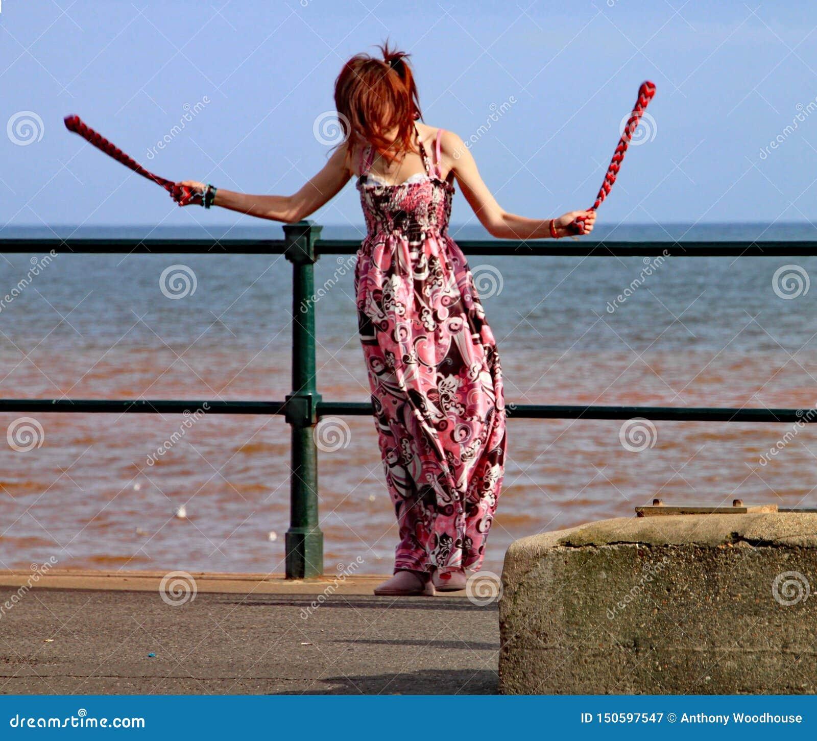 SIDMOUTH, DEVON, INGLATERRA - 5 DE AGOSTO DE 2012: Uma jovem mulher mante distraído transmissores perto com rodopiar clubes pelos