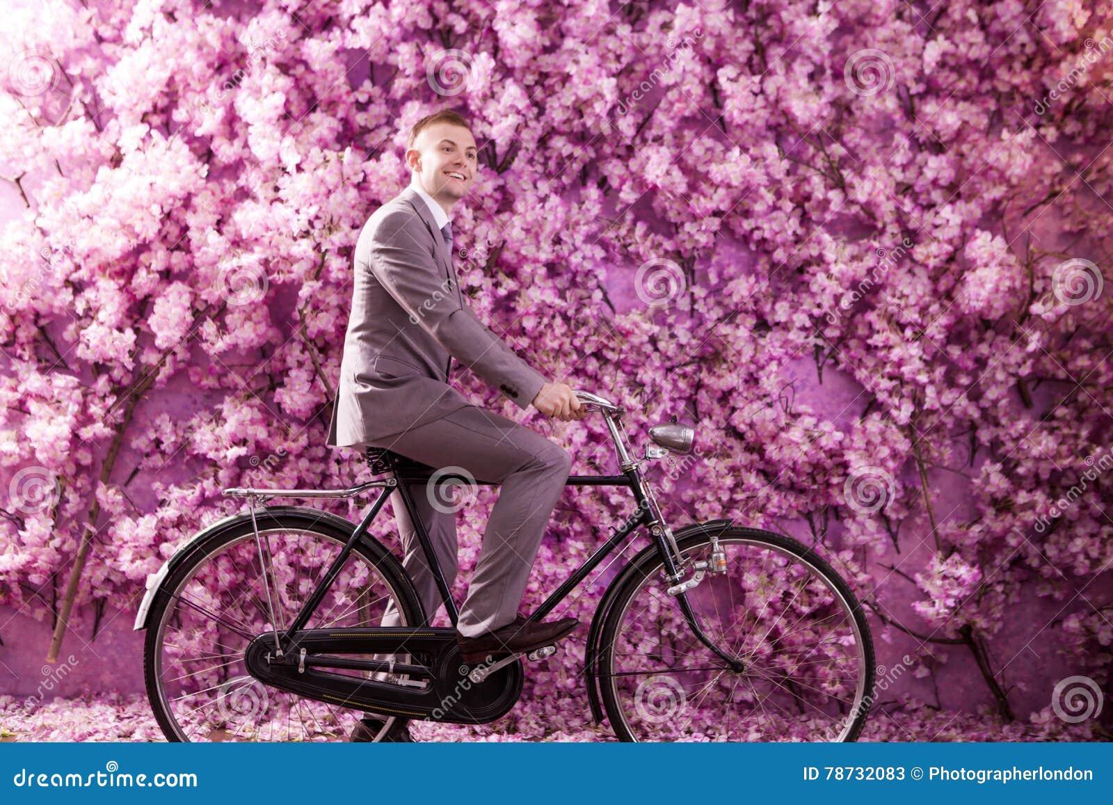 Sidosikt av att le brudgumridningcykeln mot väggen som täckas med rosa blommor