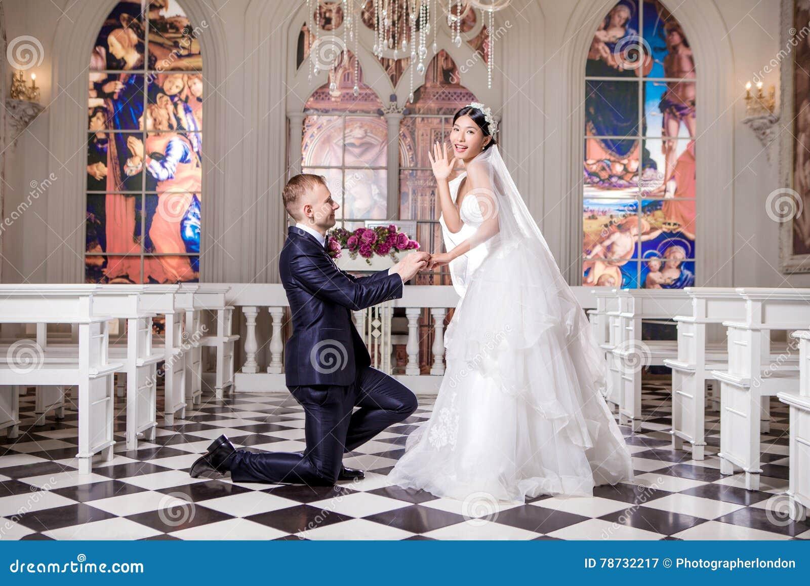 Sidosikt av brudgummen som sätter cirkeln på förvånade bruds finger i kyrka