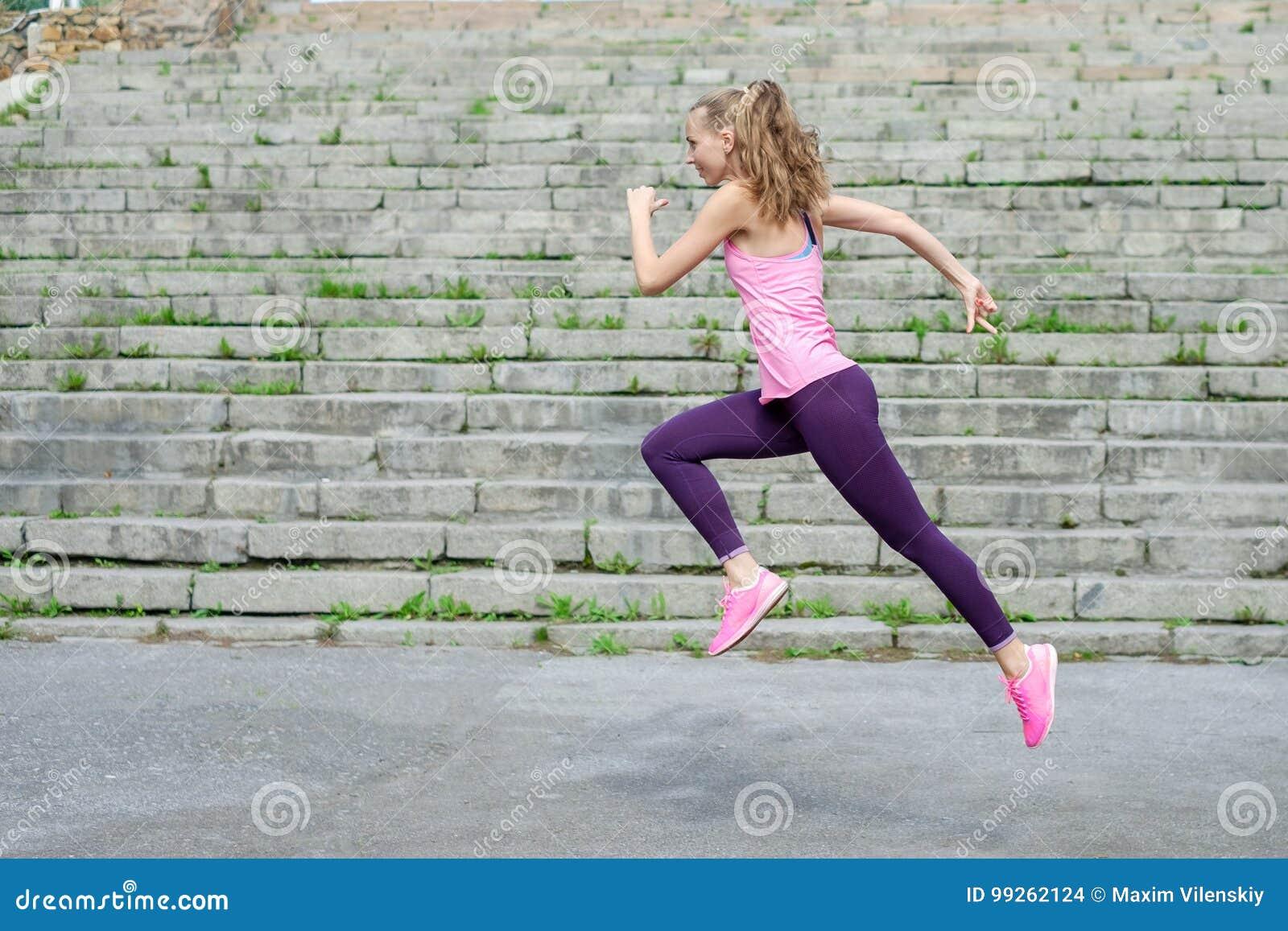 Sidosikt av den aktiva sportiga unga rinnande kvinnalöpareidrottsman nen med vikt för förlust för kondition för sport för kopieri