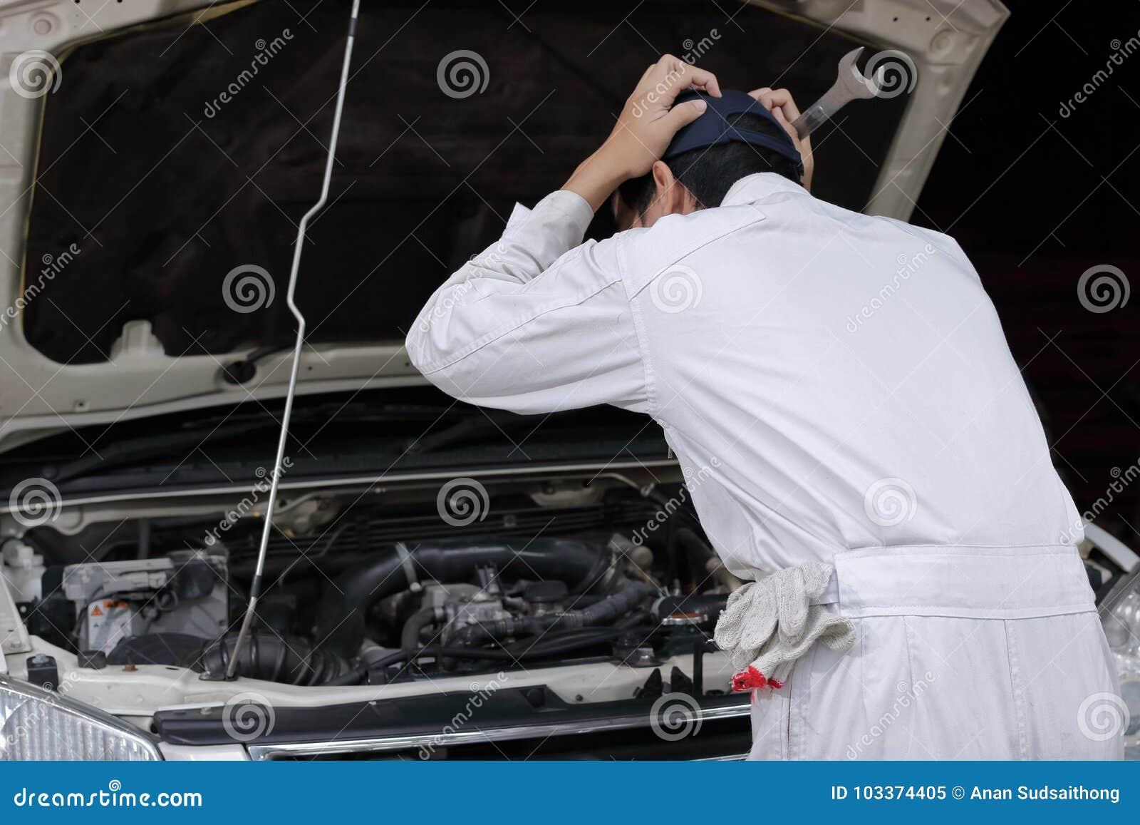 Sidosikt av den frustrerade stressade unga mekanikermannen i den vita likformign som trycker på hans huvud med händer mot bilen i