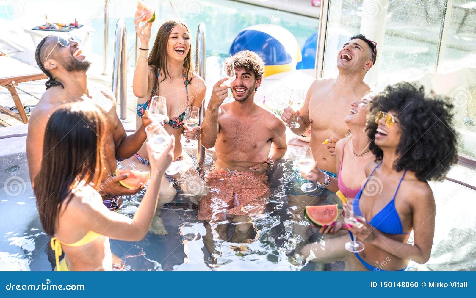 Sidosikt av den lyckliga vängruppen som dricker champagne för vitt vin på simbassängpartiet - lyxigt semesterbegrepp