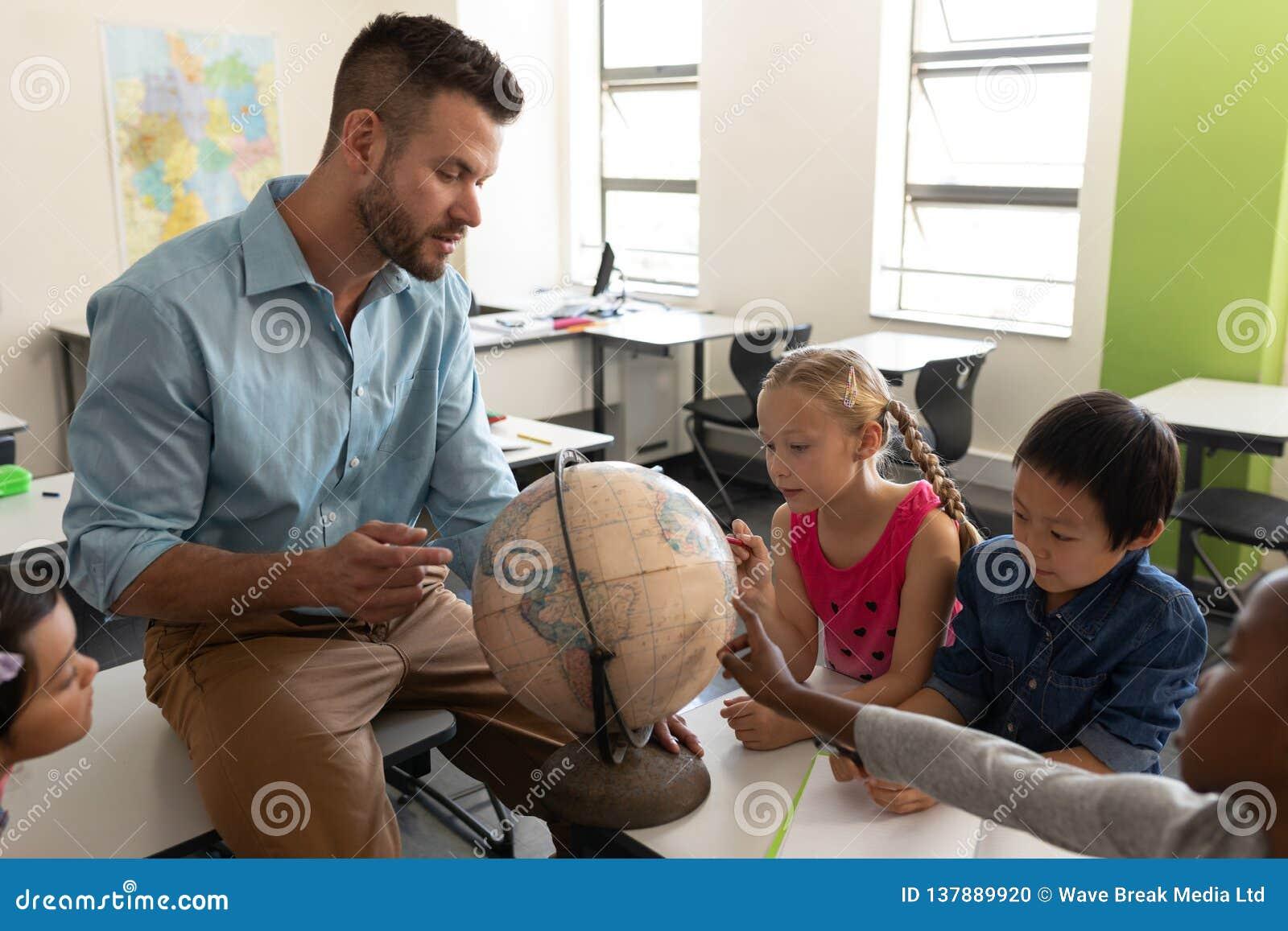 Sidosikt av den manliga läraren som undervisar hans ungar om geografi, genom att använda jordklotet i klassrum