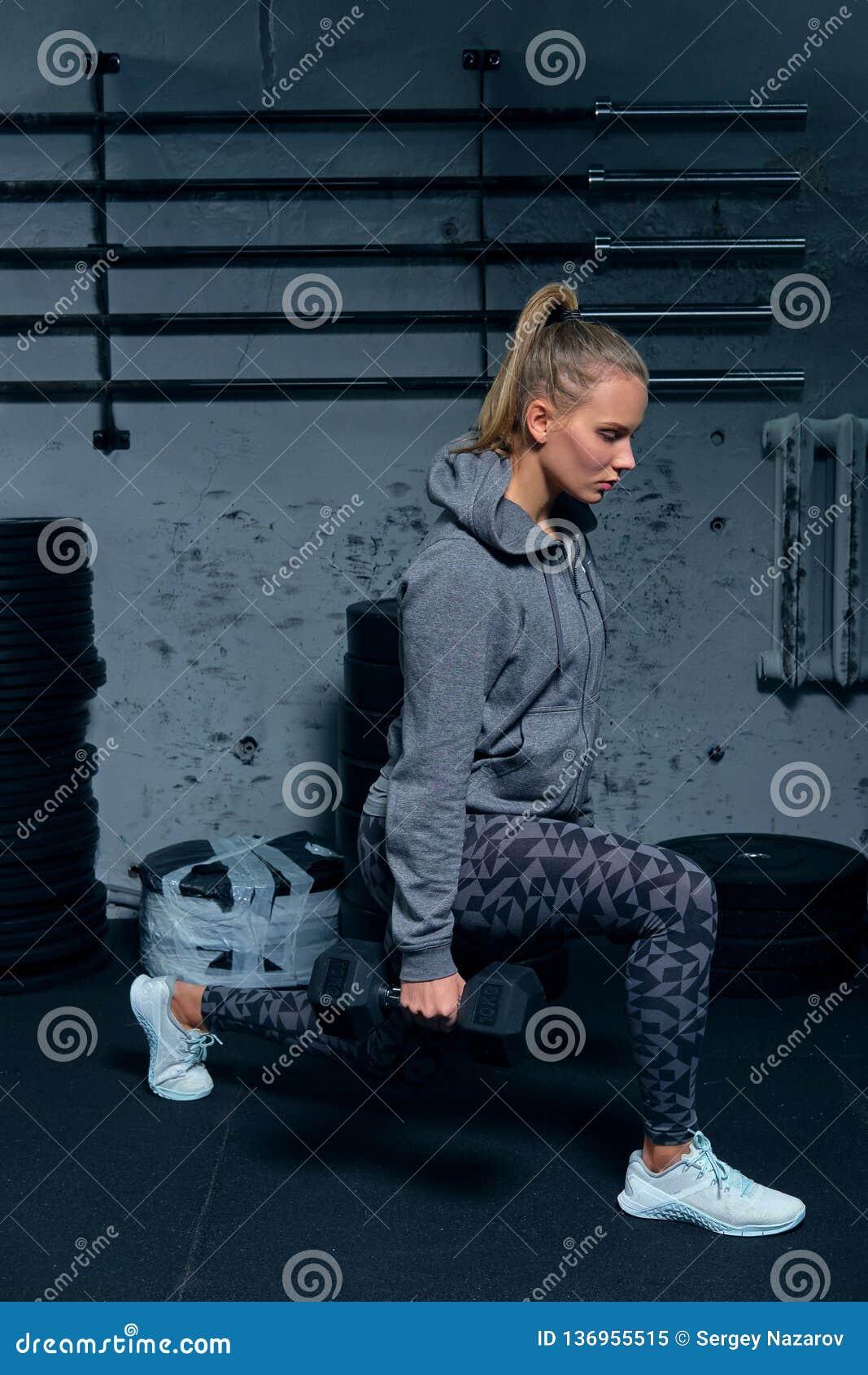 Sidosikt av en härlig konditioninstruktör för ung kvinna som bär en sportdräkt som gör på utfall för en övning med hantlar